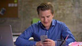 Ritratto dell'uomo d'affari biondo di mezza età che parla nel videochat facendo uso dello smartphone in ufficio stock footage