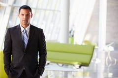 Ritratto dell'uomo d'affari che sta ricezione moderna dell'ufficio Fotografia Stock