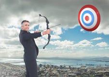 Ritratto dell'uomo d'affari che tende con l'arco e la freccia all'obiettivo sopra paesaggio urbano Fotografie Stock Libere da Diritti
