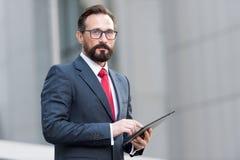 Ritratto dell'uomo d'affari con la compressa a disposizione su fondo dell'edificio per uffici Uomo d'affari facendo uso della com immagini stock libere da diritti