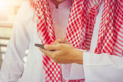 Ritratto dell'uomo d'affari del Medio-Oriente arabo sorridente facendo uso dello smartphone fotografia stock libera da diritti