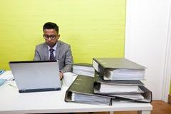 Ritratto dell'uomo d'affari indiano che lavora al suo computer portatile al suo scrittorio Fotografie Stock Libere da Diritti