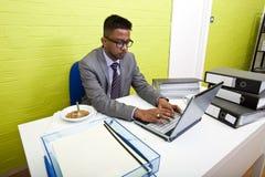Ritratto dell'uomo d'affari indiano che lavora al suo computer portatile al suo scrittorio Immagine Stock