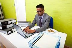 Ritratto dell'uomo d'affari indiano che lavora al suo computer portatile al suo scrittorio Fotografie Stock