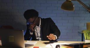 Ritratto dell'uomo d'affari malato e stanco che starnutisce mentre lavorando nell'ufficio tardi alla notte archivi video