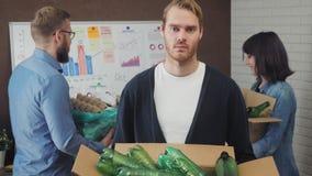 Ritratto dell'uomo d'affari nell'ufficio con il riciclaggio dei materiali archivi video