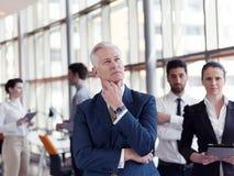 Ritratto dell'uomo d'affari senior come capo con il personale in backgrou Fotografie Stock
