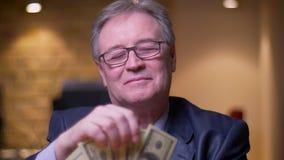Ritratto dell'uomo d'affari senior in costume convenzionale che conta soldi che sono felici e soddisfatti in ufficio stock footage