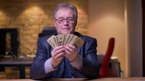 Ritratto dell'uomo d'affari senior in costume convenzionale che conta soldi che sono felici in ufficio archivi video