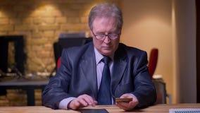 Ritratto dell'uomo d'affari senior in costume convenzionale che fa le transazioni con la carta di credito e la compressa in uffic video d archivio