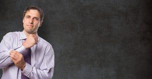 Ritratto dell'uomo d'affari sicuro che abbottona manica contro la lavagna Immagini Stock