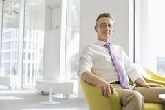 Ritratto dell'uomo d'affari sicuro che si siede all'ingresso dell'ufficio Fotografia Stock
