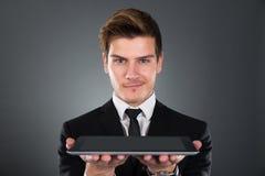 Ritratto dell'uomo d'affari sicuro che tiene compressa digitale Immagini Stock Libere da Diritti