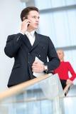 Ritratto dell'uomo d'affari sicuro e motivato con il telefono cellulare Fotografie Stock