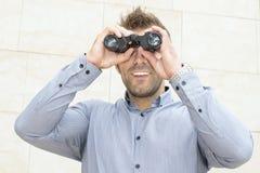 Ritratto dell'uomo d'affari sorridente che guarda tramite il binocolo. fotografia stock libera da diritti