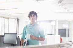 Ritratto dell'uomo d'affari sorridente che mangia caffè in ufficio creativo fotografia stock libera da diritti