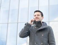 Ritratto dell'uomo d'affari sorridente che parla dal telefono, all'aperto. Immagine Stock