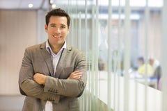 Ritratto dell'uomo d'affari sorridente che sta nel corridoio Immagini Stock Libere da Diritti