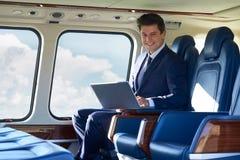 Ritratto dell'uomo d'affari Working On Laptop nella cabina Du dell'elicottero Fotografie Stock