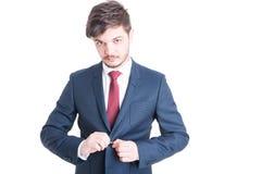 Ritratto dell'uomo di affari che chiude il suo rivestimento del vestito Immagini Stock