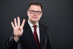 Ritratto dell'uomo di affari che indossa vestito nero che mostra numero quattro fotografie stock