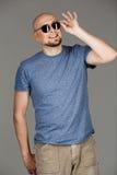 Ritratto dell'uomo di mezza età bello sicuro in camicia grigia ed occhiali da sole che posano sopra il fondo scuro Fotografia Stock Libera da Diritti