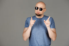 Ritratto dell'uomo di mezza età bello sicuro in camicia grigia ed occhiali da sole che posano sopra il fondo scuro Fotografie Stock