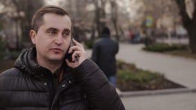 Ritratto dell'uomo di mezza età che chiama dal telefono sulla via in autunno archivi video