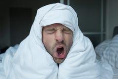 Ritratto dell'uomo di sbadiglio su un letto Riguarda la sua testa di coperta Fotografie Stock