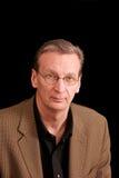 Ritratto dell'uomo di sguardo curioso più anziano sul nero Fotografie Stock Libere da Diritti