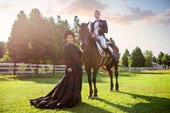 Ritratto dell'uomo facente una pausa della donna che si siede sul cavallo al campo durante il tramonto Fotografia Stock