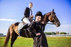 Ritratto dell'uomo facente una pausa della donna sicura che si siede sul cavallo al campo Fotografia Stock Libera da Diritti