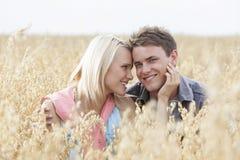 Ritratto dell'uomo felice che si siede con la donna romantica in mezzo del campo immagini stock