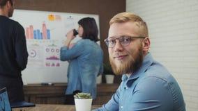 Ritratto dell'uomo felice che si siede nell'ufficio che lavora al suo computer portatile video d archivio