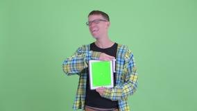 Ritratto dell'uomo felice del nerd che mostra compressa digitale e che sembra sorpreso video d archivio