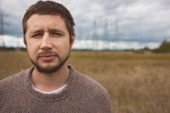 Ritratto dell'uomo forte adulto con la barba al prato di autunno, piloni di energia su fondo Fotografia Stock
