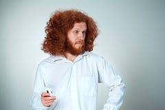 Ritratto dell'uomo imbarazzato che parla sul telefono un fondo grigio Fotografie Stock