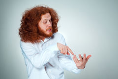Ritratto dell'uomo imbarazzato che parla sul telefono un fondo grigio Fotografia Stock Libera da Diritti