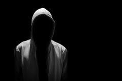 Ritratto dell'uomo invisibile in cappuccio isolato sul nero Immagini Stock