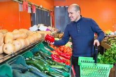 Ritratto dell'uomo maturo che acquista le verdure stagionali in alimento dell'azienda agricola Immagine Stock