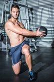 Ritratto dell'uomo muscolare che fa esercizio con palla medica Immagini Stock