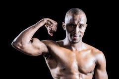 Ritratto dell'uomo muscolare che sorride mentre flettono muscles Immagine Stock