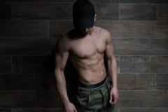 Ritratto dell'uomo muscolare che sta vicino alla parete fotografia stock