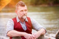 Ritratto dell'uomo nel suo 50s che si siede dal fiume Fotografia Stock Libera da Diritti