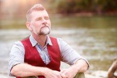 Ritratto dell'uomo nel suo 50s che si siede dal fiume Fotografie Stock Libere da Diritti