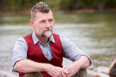 Ritratto dell'uomo nel suo 50s che si siede dal fiume Fotografia Stock