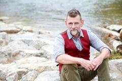 Ritratto dell'uomo nel suo 50s che si siede dal fiume Immagini Stock Libere da Diritti