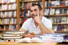 Ritratto dell'uomo pensieroso in una libreria Fotografia Stock Libera da Diritti