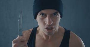 Ritratto dell'uomo pericoloso in un cappuccio con un coltello stock footage