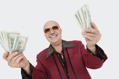 Ritratto dell'uomo senior allegro che mostra le banconote degli Stati Uniti contro il fondo grigio Immagini Stock